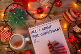 """All I want for Christmas is…"" text on notebook written by young woman with colorful gloves in festive decor"