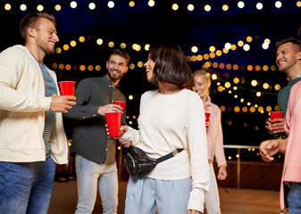 leisure, celebration and people concept - happy friends with drinks dancing at rooftop party at night with blurred bokeh lights