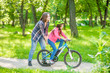 Leinwanddruck Bild - Happy family. Smiling mom teaches her daughter to ride a bicycle in the park