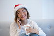 Positive pretty woman in Santa hat talking on mobile phone and drinking coffee at home. Smiling Asian lady in casual clothing having phone conversation. Communication concept