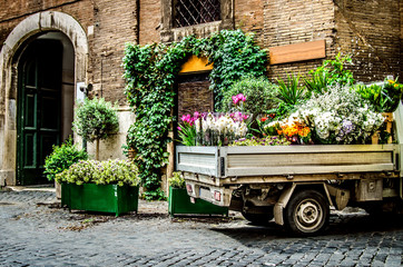 A truck filled with flowers on a Roman street. Rome. Italy