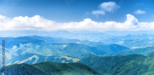 Panorama of blue mountains and hills with sky and clouds