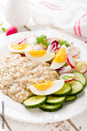 Leinwandbild Motiv Oatmeal porridge with boiled egg and vegetable salad with fresh radish, cucumber and lettuce. Healthy dietary breakfast