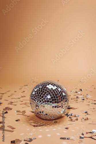 shiny silver disco ball and confetti on beige - 236289439
