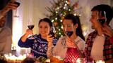 holidays and celebration concept - happy friends having christmas dinner party at home, drinking red wine and clinking glasses - 236290649