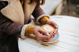 Close-up image of young woman drinking coffee outdoors.