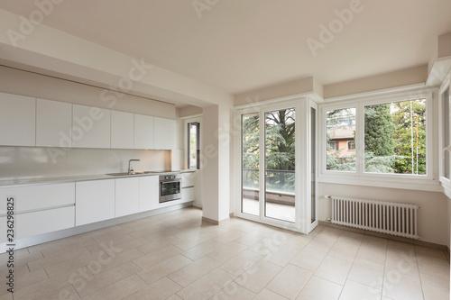 Otwarta przestrzeń z dużymi oknami i nowoczesną kuchnią