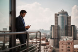 Take a pause. Full length portrait of smiling businessman reading massages on smartphone while standing on office terrace. Copy space on right - 236317626