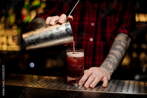 Leinwanddruck Bild Tattooed barman pouring sweet juicy cocktail into a glass on bar