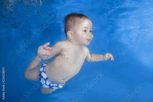 Boy swim underwater in the swimming pool on a blue water background. Healthy family lifestyle and children water sports activity. Child development, disease prevention