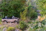 Old abandoned rusty explorers jeep in tropical rainforest