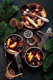 hot mulled wine cooked in two saucepan with spices, orange and cranberries on the table with Christmas fir twigs on a dark background - 236344012
