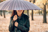 Woman under umbrella posing in autumn park. Bright yellow leaves and trees. - 236356031