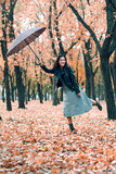 Woman with umbrella posing in autumn park. Bright yellow leaves and trees. She imitates the wind. - 236356069