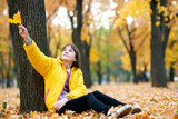 Teen girl sits near tree in autumn park and plays with big maple's leaf. Bright yellow leaves and trees. - 236356240