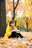 Sad teen girl sits near tree in autumn park. Bright yellow leaves and trees. - 236356403