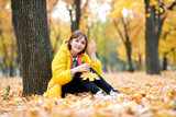 Teen girl sits near tree in autumn park and plays with big maple's leaf. Bright yellow leaves and trees. - 236356446