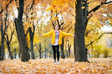 Happy teen girl is running in autumn park with big maple's leaf. Bright yellow leaves and trees. - 236356497