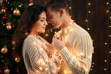 young couple is in christmas decoration and lights, fir tree on dark wooden background, new year holiday concept - 236357000
