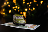 Green car and banknote United States One Hundred Dollar under the New Year tree