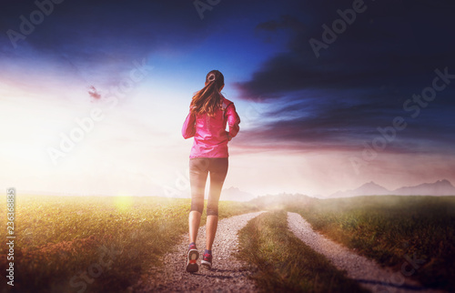 Leinwanddruck Bild Woman running in fit wear in majestic landscape