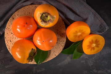 Ripe persimmon fruits in a cork plate