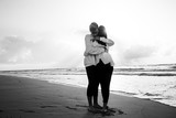 Black and white photo of a young couple in love by the sea