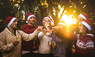 Friends group with santa hats celebrating Christmas with champagne wine toast outdoors - Tropical holidays concept with young people enjoying time and having fun together with sparkles at sunset