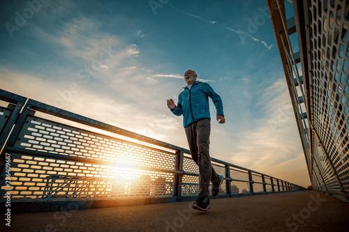 Leinwanddruck Bild Senior man running  in the city