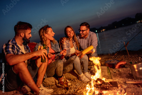 Friends having picnic around the fire