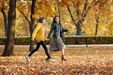 Two happy girls running in autumn city park. - 236413620
