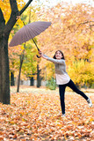 Teen girl with umbrella posing in autumn park. Bright yellow leaves and trees. She imitates the wind. - 236413843