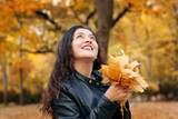 Pretty woman is posing with bunch of maple's leaves in autumn park. Beautiful landscape at fall season. - 236414099