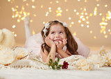 girl child with rose flower is posing in christmas lights, yellow background, pink dress - 236414208