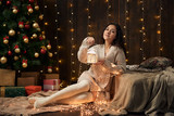 young girl is in christmas lights and decoration, dressed in white, fir tree on dark wooden background, winter holiday concept - 236414252