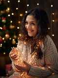 young girl is in christmas lights and decoration, dressed in white, fir tree on dark wooden background, winter holiday concept - 236414271