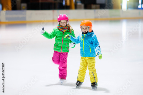 Child skating on indoor ice rink. Kids skate. - 236417407