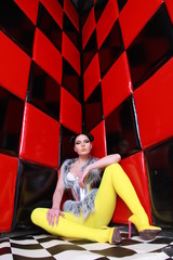 crazy fashion girl wearing yellow pantyhose, silver furwaistcoat and futuristic steel belt posing near red wall with black squares alone