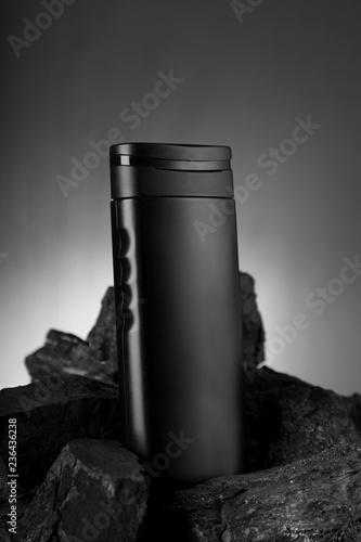 Czarna pusta butelka produktu na czarny kamień do makiet