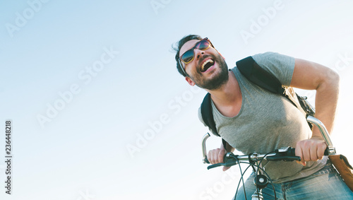 Active sport man with excited face expression exploring and traveling by mountain bike on the road. Vintage film filter style image.