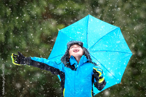 Leinwanddruck Bild Snow falling on boy with umbrella catching snowflakes on tongue