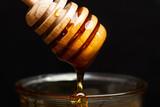 Miel con batuta cayendo en cuenco de cristal