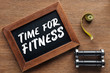 measuring tape, dumbbells and wooden chalk board with 'time for fitness' quote, dieting and healthy lifesyle concept
