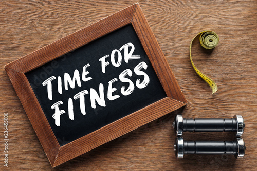 Foto Murales measuring tape, dumbbells and wooden chalk board with 'time for fitness' quote, dieting and healthy lifesyle concept