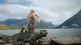 Traveling in Scandinavia - a woman photographs a picturesque alpine lake in Norway - 236469465