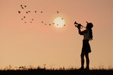 Woman play trumpet with sunset or sunrise background