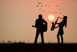musician play guitar and saxophone with sunset or sunrise background