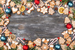 Leinwandbild Motiv Christmas frame made of gingerbread cookies, anise stars, berries, candy cane lollipops, Christmas balls, orange chips and rosemary on wooden background. Flat lay.