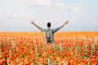 Happy traveler man standing in poppies flowers meadow.