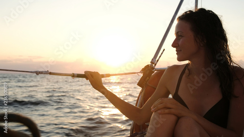 Happy young woman in a swimsuit sits on the aft of a sailing yacht at sunset.